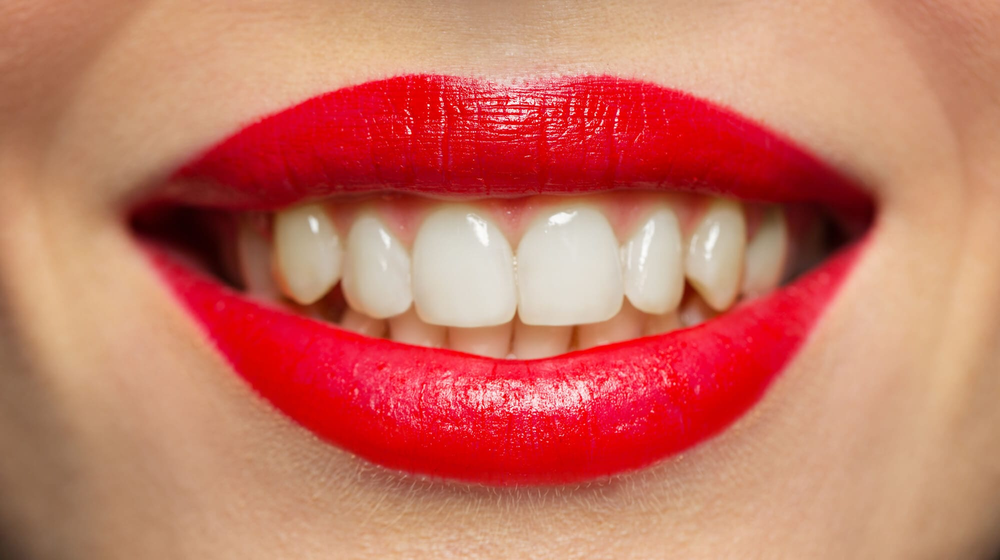 lips or mouth of smiling woman with red lipstick